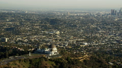 Aerial view of Griffith Park Observatory and distant City Los Angeles Stock Footage