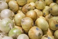 Yellow onions crop from market shelves real with flaws and bruis Stock Photos