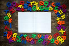 Exercise-book with plastic letters and numbers - stock photo