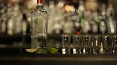 4K Smiling barman pouring liquor into row of shot glasses Stock Footage