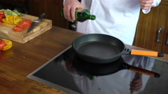 Сhef cook is pouring olive oil on the frying pan  Stock Footage