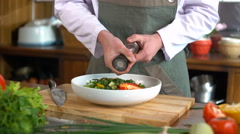 Сhef cook peppers salad in a bowl on the wooden table Stock Footage