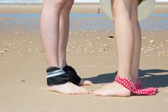 Legs of couple at the sea with bikini down and hat Stock Photos