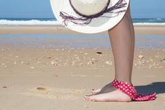 Woman at the beach holding hat having bikini on foot - stock photo