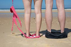 Legs of couple at the sea with bikini down and hat - stock photo