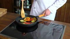 Сhef cook stirs vegetables with a wooden blade on the frying pan Stock Footage