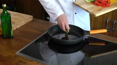 Сhef cook is cooking vegetables on the frying pan  Stock Footage