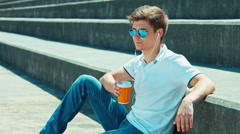 Student male in sunglasses and headphones holding cup of tea and drinking tea Stock Footage