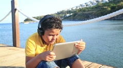 Boy playing digital tablet  computer on wooden pier by the sea 2 Stock Footage