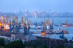 Sea commercial port at night against working steel factory in Mariupol - stock photo