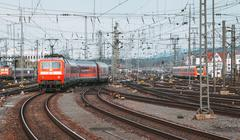 Railway station with modern red commuter train at sunset Stock Photos