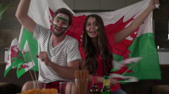 Thrilled welsh soccer fan couple at home cheering for wales Stock Footage