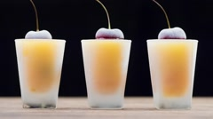 Frozen cherries. Cold orange drink Stock Footage