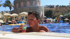 Child drinking summer drinks juice in pool 2 Stock Footage