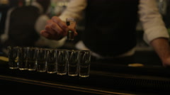 4K Barman pouring flaming liquor into row of shot glasses setting them alight - stock footage