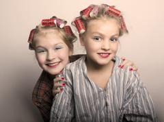 two teenager girls playing Housewives, do yourself hairstyles and makeup having - stock photo