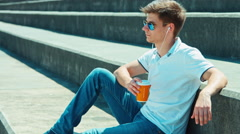 Beautiful student male in sunglasses and headphones  drinking tea Stock Footage