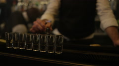 4K Barman pouring flaming liquor into row of shot glasses setting them alight Stock Footage