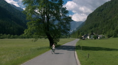 Aerial - Flying in front of a woman in white dress riding bicycle on rural road Stock Footage