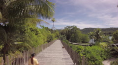 Flight over a woman walking on a long wooden path way through a tropical jungle Stock Footage