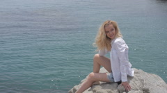 Sexy young blonde woman in sundress sitting on rocks at the beach with ocean Stock Footage