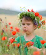 Happy cute child girl on poppies field. Happy children. Healthy lifestyle Stock Photos