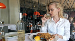 Smiling pretty blonde woman a large glass of wine in her hand Stock Footage