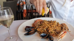 Paella with rice and seafood, delicious food. Lemon squezze by girl in Stock Footage