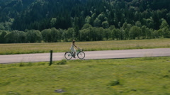 Aerial - Young woman in a white dress riding bicycle on a rural road Stock Footage