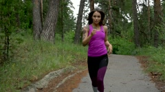 Fitness workout outdoors. Sport woman running through the woods. slow motion. Stock Footage