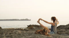 Woman and dog doing yoga and gymnastics workout at rocky beach at summer. - stock footage