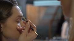 Make-up artist doing professional make-up to a girl - stock footage
