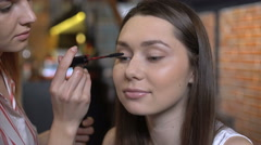 Makeup artist doing make up using cosmetic brush applying eye shadow - stock footage