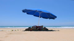 Baby and mother lying down blue parasol at beach Stock Footage