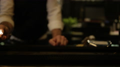 4K Barman using a match to set light to row of shot glasses with clear liquor Stock Footage