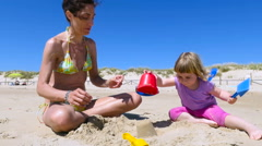 Baby and mother sitting on sand beach playing with bucket Stock Footage