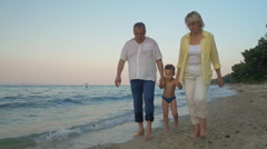 Grandparents and grandchild walking on the beach Stock Footage