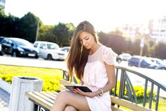 Beautiful brunette holding a plate,  bright sunny day, on  bench, fashion style Stock Photos