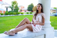 Beautiful brunette girl resting in the open air sitting, dreaming about the man - stock photo