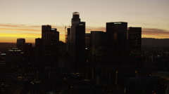 Aerial sunset silhouette of Bank of America building downtown Los Angeles Stock Footage