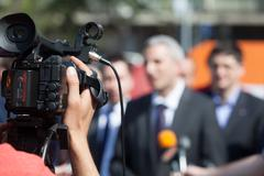 filming an news event with a video camera - stock photo