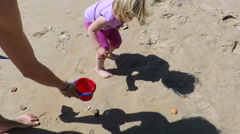 Baby collecting sea shells with woman Stock Footage