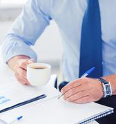 businessman drinking coffee in office - stock photo