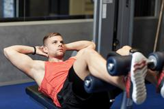 young man making abdominal exercises in gym - stock photo