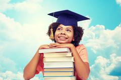happy african bachelor girl with books over sky - stock photo
