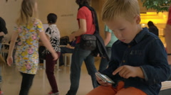 Kid looking at photos on mobile phone in trade centre Stock Footage