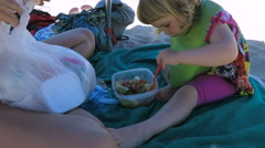 Baby next to mother at beach eating salad Stock Footage