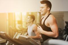 smiling men exercising on treadmill in gym - stock photo