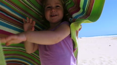 baby playing and wrapping in beach colorful towel slow motion - stock footage