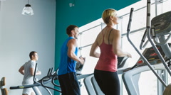 Woman and two man exercising at the gym on a cross trainer Stock Footage